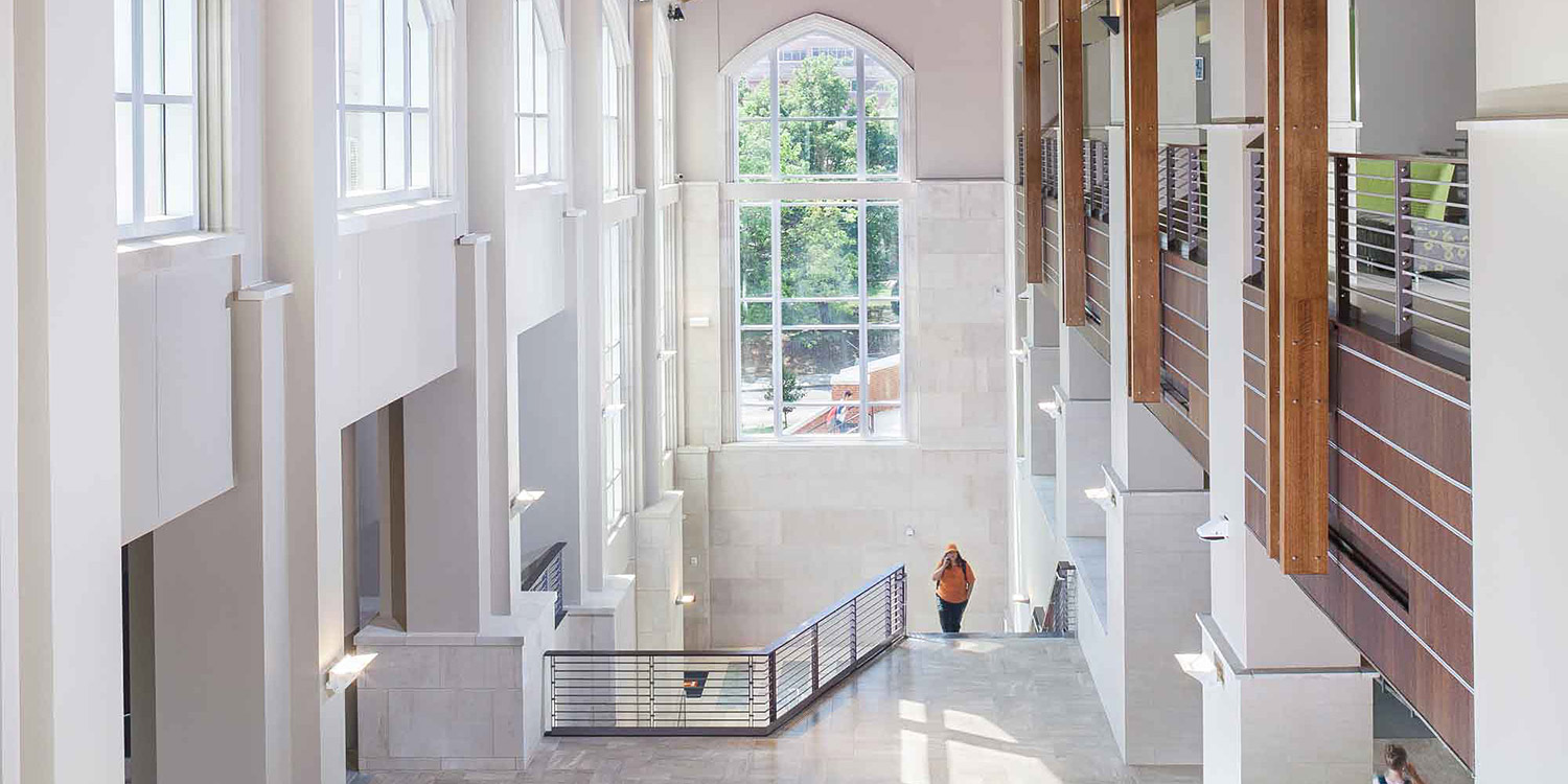 Student climbs stairs inside Strong Hall.